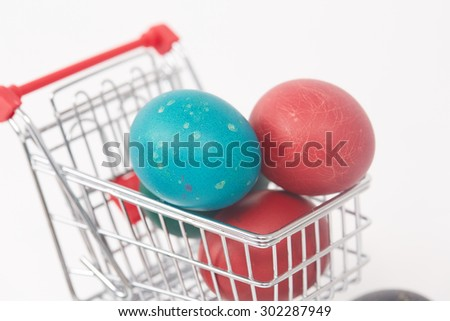 Easter colorful painted eggs in the shopping cart and near the trolley