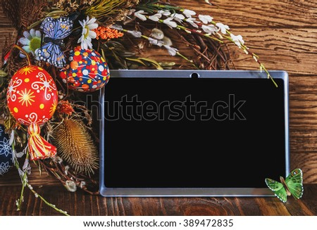Easter composition. Holiday wreath with colored eggs and tablet pc with blank screen on a wooden table. Easter theme - stock photo