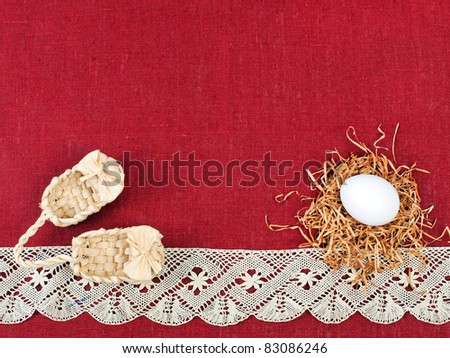 Easter composition: nest with one white egg and small wicker shoes on wine red flax background decorated with lace (with space for text) - stock photo