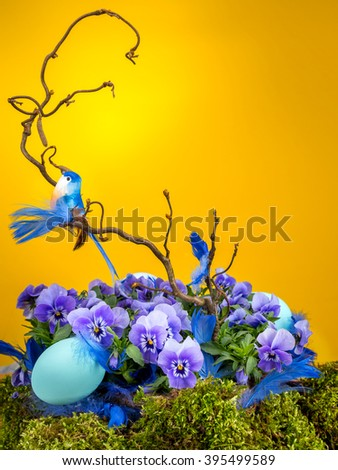 Easter composition with blue bird sitting on tree branch with violet flowers end blue egg shot on yellow background - stock photo