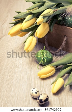 Easter composition with yellow tulips and Easter eggs on wooden table. This image is toned.