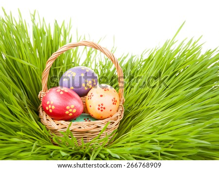 Easter concept. Eggs in a basket in the grass isolated on white background.