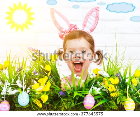 Easter concept. Happy funny  child girl in a costume bunny with grass and flowers - stock photo