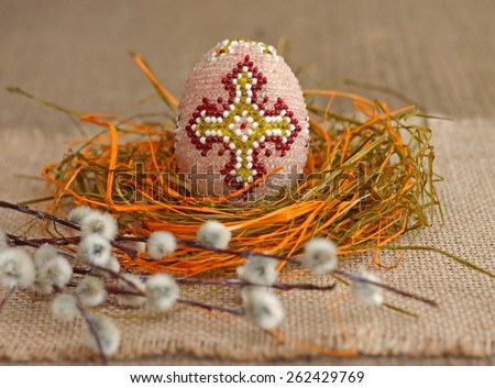 Easter concept. Image of beaded egg and willow twig - stock photo