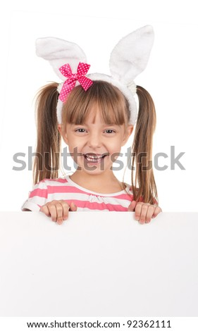 Easter concept image. Portrait of happy little girl with bunny ears and empty white board over white background. - stock photo