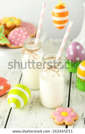 Easter cookies and eggs with bottle of milk on white wooden background - stock photo
