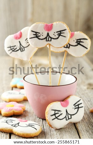 Easter cookies in cup on grey wooden background - stock photo