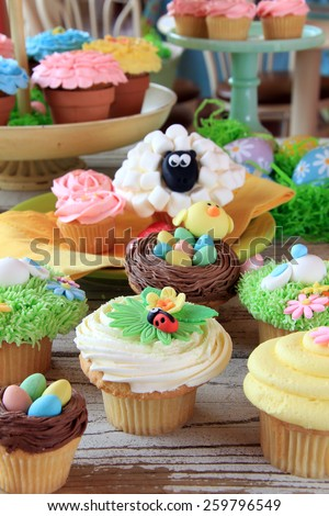 Easter cupcake display at a bakery. Shallow dof, focus on the front cupcakes.  - stock photo