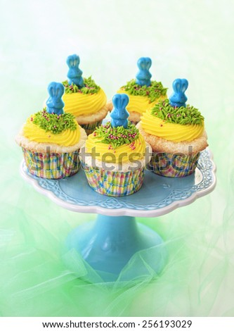 Easter cupcakes. Angel food cupcakes with yellow vanilla frosting and blue candy bunnies. - stock photo
