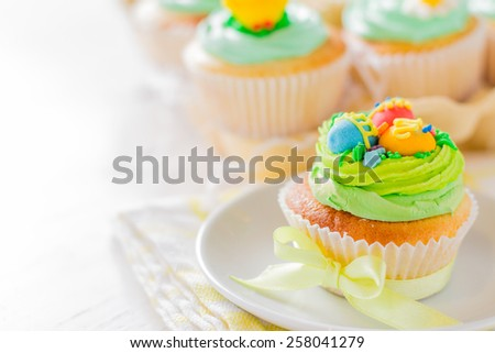 Easter cupcakes decorated with eggs sugar figures on white plate, yellow ribbon, plaid napkin, white wood background - stock photo