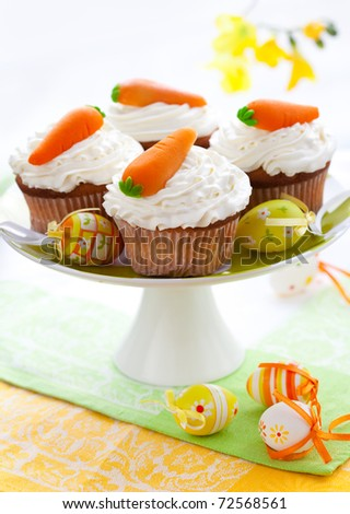 Easter  cupcakes with marzipan carrots on a cake stand - stock photo