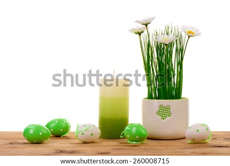 Easter decor candles, eggs and flowers in pot on the wooden background. - stock photo