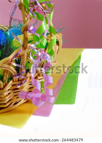 Easter decor is closeup of an Easter basket filled with grass and plastic eggs. The basket is adorned with pink and green ribbons. There are layers of yellow, pink and green paper. Background is pink - stock photo