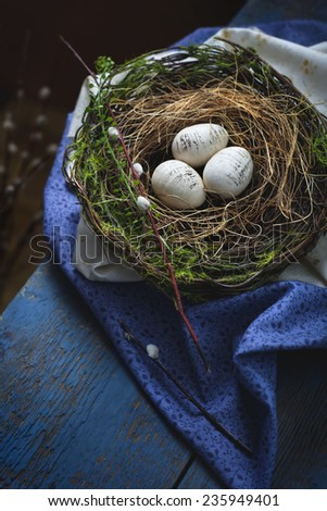 Easter decoration - a nest with wooden eggs - on an old wooden table. Dark photo with space for text. Toned photo. - stock photo