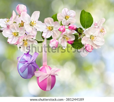 Easter decoration. Apple blossom and Easter eggs on defocused of natural background of blooming trees - stock photo