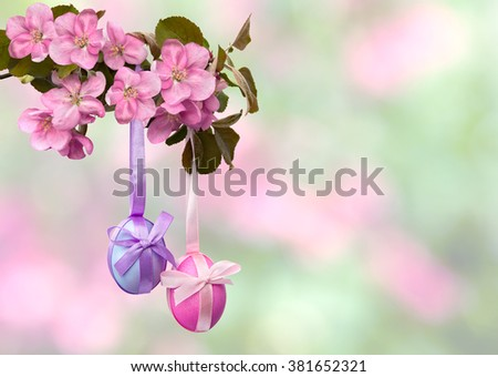 Easter decoration. Apple blossom and Easter eggs on defocused of natural background of blooming trees with space for text. - stock photo