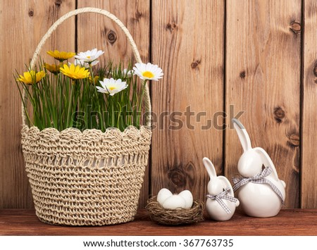Easter decoration- bunnies with easter eggs in the nest on the wooden background. - stock photo