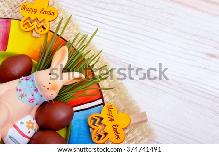 Easter decoration  bunny with chocolate eggs on wooden background.