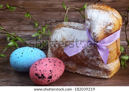 Easter decoration - card / easter lamb cake with purple ribbon, easter eggs and willow sticks on wooden table / desk - stock photo