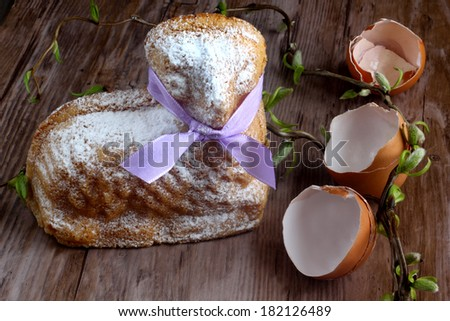 Easter decoration - card / easter lamb cake with purple ribbon, easter eggshells and willow sticks on wooden table / desk - stock photo