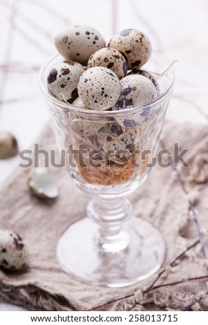 Easter decoration. Quail eggs in a glass, decoration straw and willow. selective focus  - stock photo