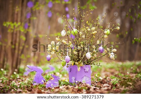 Easter decoration with easter rabbit  in the garden. Spring bouquet of blossoming willow with easter egg. - stock photo
