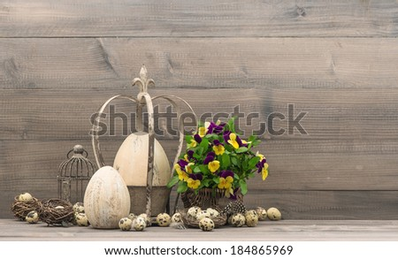easter decoration with eggs, pansy flowers, nest and birdcage. vintage style picture - stock photo