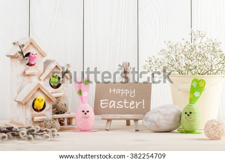 Easter decoration with greeting message on wooden background - stock photo