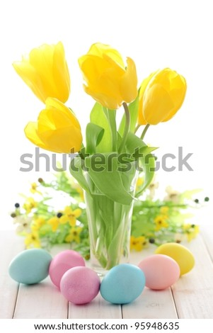 Easter decoration with painted eggs and yellow tulips. - stock photo