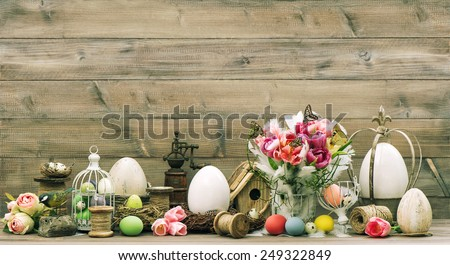 Easter decoration with pink tulip flowers and colored eggs. Vintage home interior. Retro style toned picture - stock photo