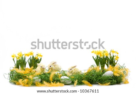 Easter decoration with straw rabbits, eggs and daffodils flowers