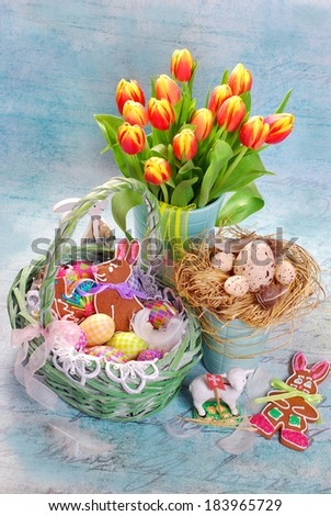 easter decoration with wicker basket,eggs,gingerbread cookies and fresh yellow-red tulips on vintage blue background - stock photo