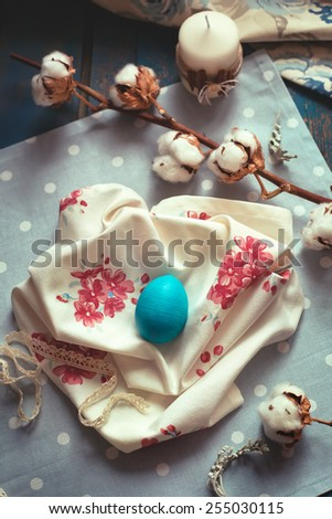 Easter decoration - wooden egg on fabric napkins, with cotton branches, retro country style setting with natural light. Toned photo. - stock photo