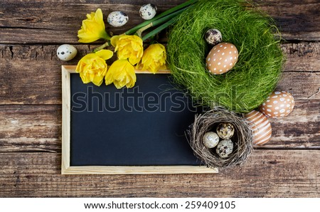 Easter decorations and black board with copy space on wooden background. - stock photo