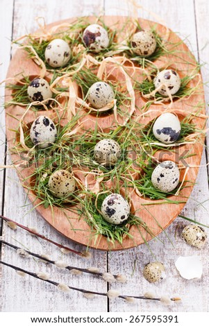 Easter decorations. Quail eggs in the nest and the grass on a wooden stand,decorated with willow. - stock photo