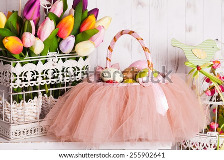 Easter decorations - spring flowers and eggs in tutu basket - stock photo