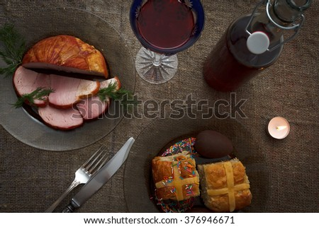Easter dinner served on burlap tablecloth. Meat, hot cross buns, chocolate eggs and wine, horizontal top view - stock photo
