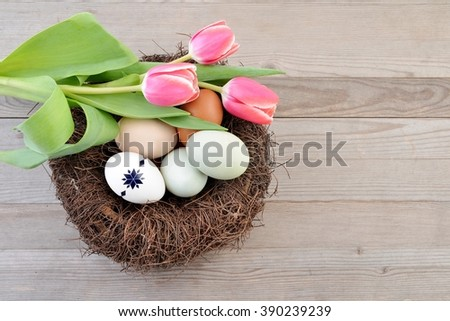 Easter. Easter background with easter eggs and tulips. Copy space, for easter text. Easter card, easter flower. Easter eggs in easter nest. - stock photo