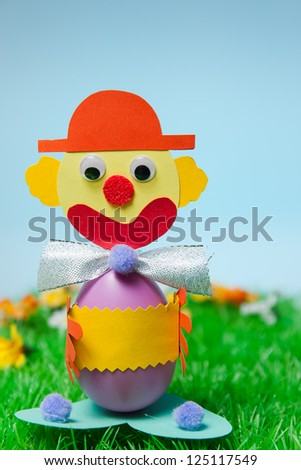 Easter egg as a clown on a well-kept lawn in front of blue heaven