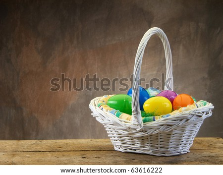 Easter egg basket on wood table and tan background with copy space - stock photo