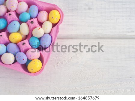 Easter Egg Candies in a Pink Egg Carton on Rustic White Board Background viewed from top or above with space or room for text, copy, or words.  Horizontal  - stock photo