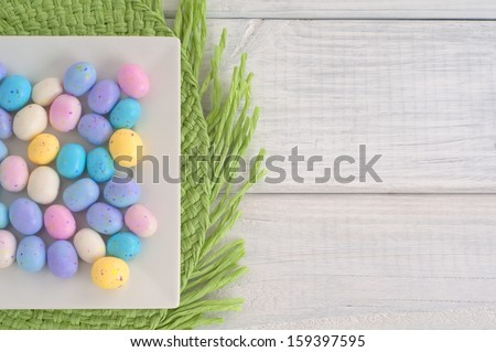 Easter Egg Candy on Square Dish on Green Placemat and White Wood Boards with Background Room or Space for copy, your words or text, overhead view  - stock photo