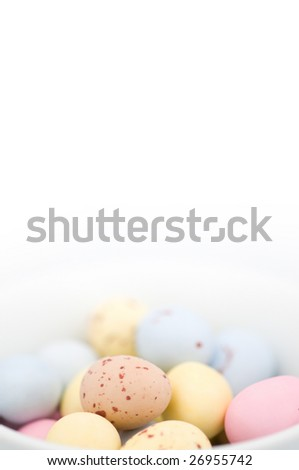 Easter egg chocolate candies on white background and in white bowl. There are some blue, yellow, pink and beige ones.