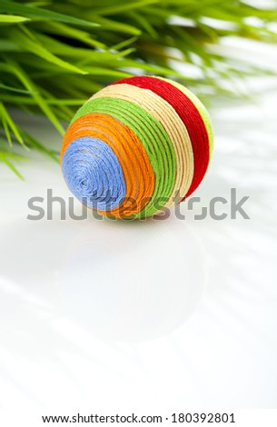 Easter egg covered with various colors wool-len yarn. Green grass in background. Space for text. - stock photo
