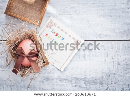 easter egg decorated with ribbon and card on wooden background - stock photo