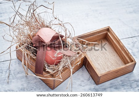 easter egg decorated with ribbon on wooden background - stock photo