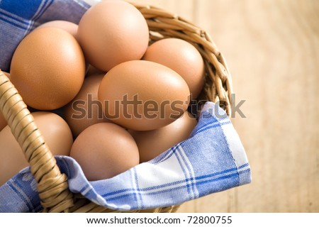 Easter egg in a basket with blue cloth. All on wodden table - stock photo