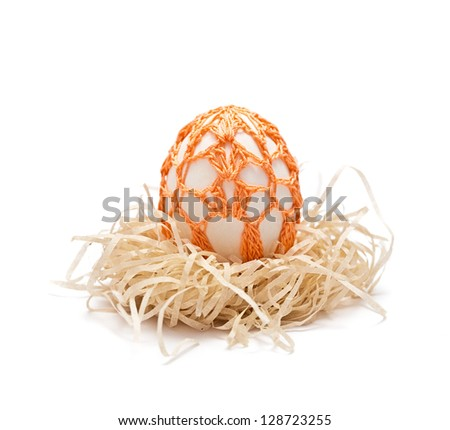 Easter egg  in a nest. Orange ornament is knitted by a hook. Isolated on a white background