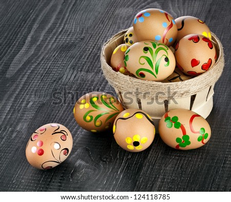 easter egg in basket  on black wooden background with copy space for your text - stock photo