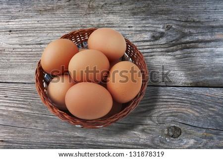 Easter egg in basket on vintage wooden background - stock photo